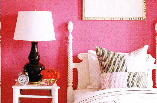 Close-up of a bed and nightstand in a raspberry pink bedroom.