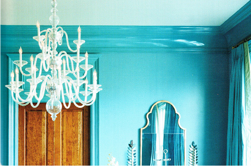 Upper corner of a bright turquoise dining room with chandelier.