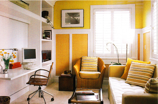 Home office in golden tones with wicker furniture and built-in workspace..
