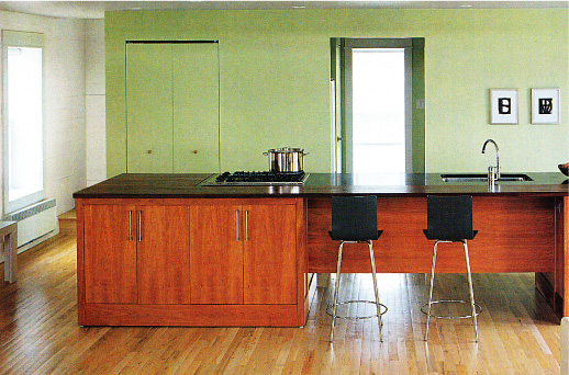 Modern kitchen in avocado green with sleek, wood island.