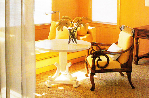 Golden yellow sitting room with filmy drapes and ornate chair.