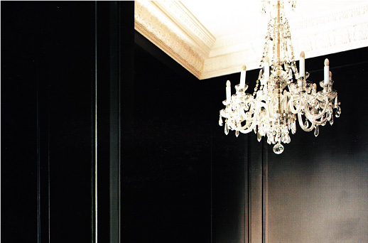 Close-up of a crystal chandelier in a black room with white crown moulding.